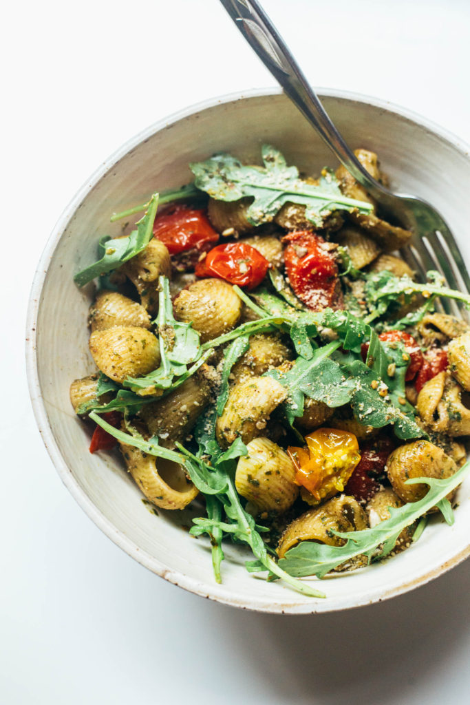 Simple summer pasta with arugula pesto, crunchy sunflower seeds, and golden roasted tomatoes. Dinner in under 30