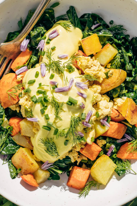 Close up of golden vegan hollandaise made with cashews on a breakfast bowl with herbs, scramble, and yams