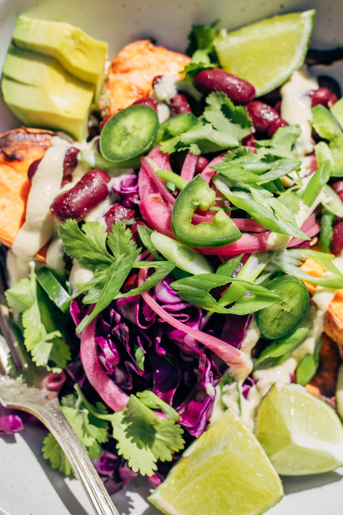 Close up of baked Mexican style yam with beans, jalapeños, purple cabbage, and cashew sauce.