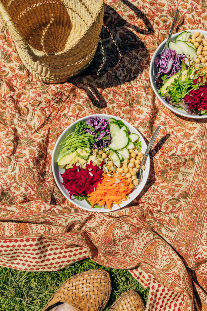 Vegan Hippie Salad with nutritional yeast ginger dressing arranged on a brightly coloured picnic blanket