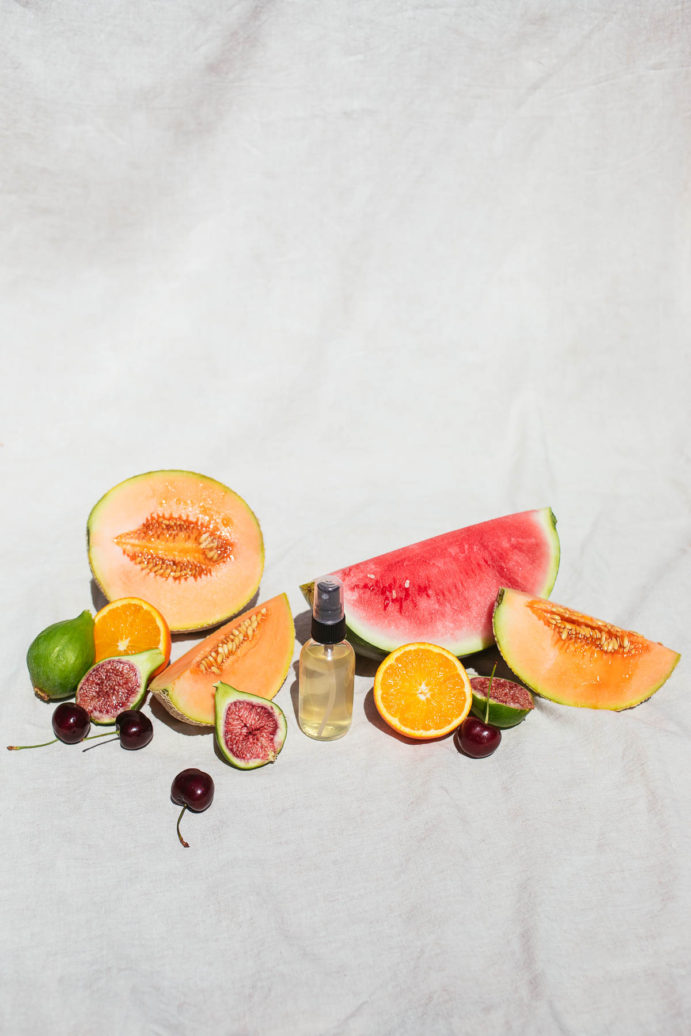 Image of face toner with summer fruit on a white backdrop