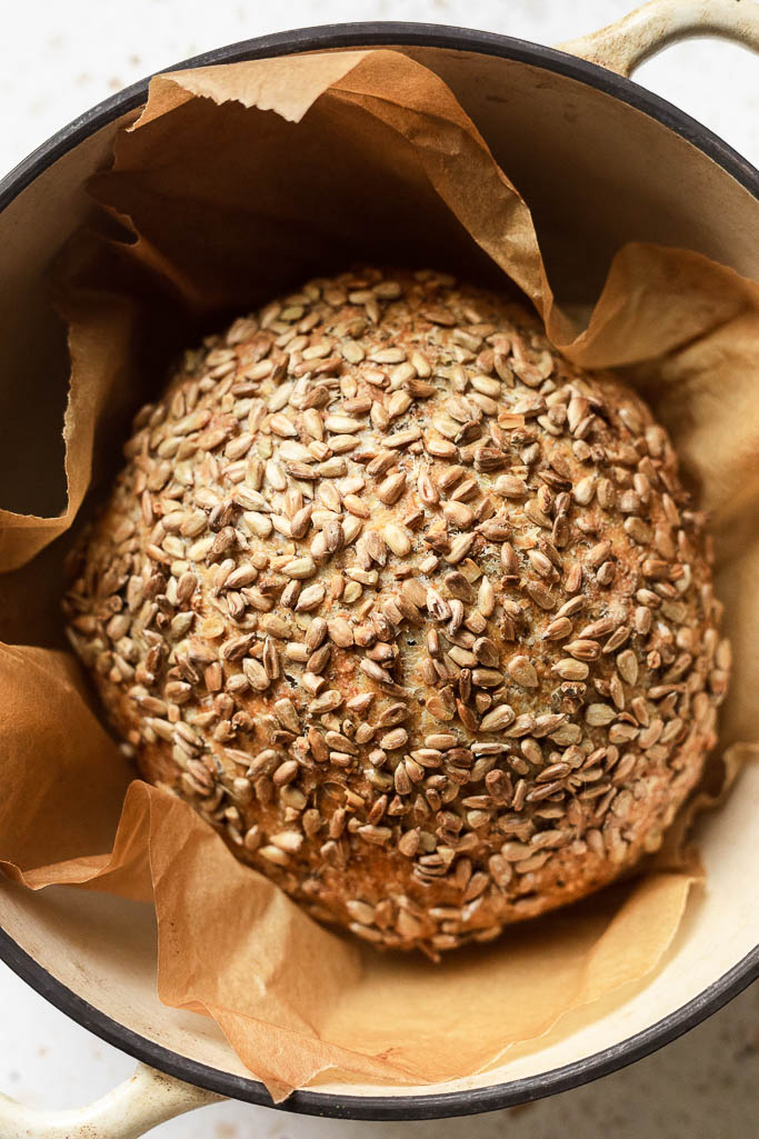 Close up of cooked protein bread covered in sunflower seeds, in a dutch oven