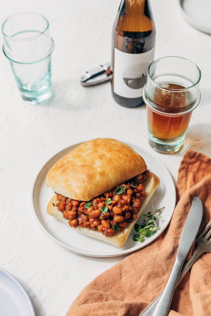 Close up of vegan baked beans served on a bun on a table with beer.
