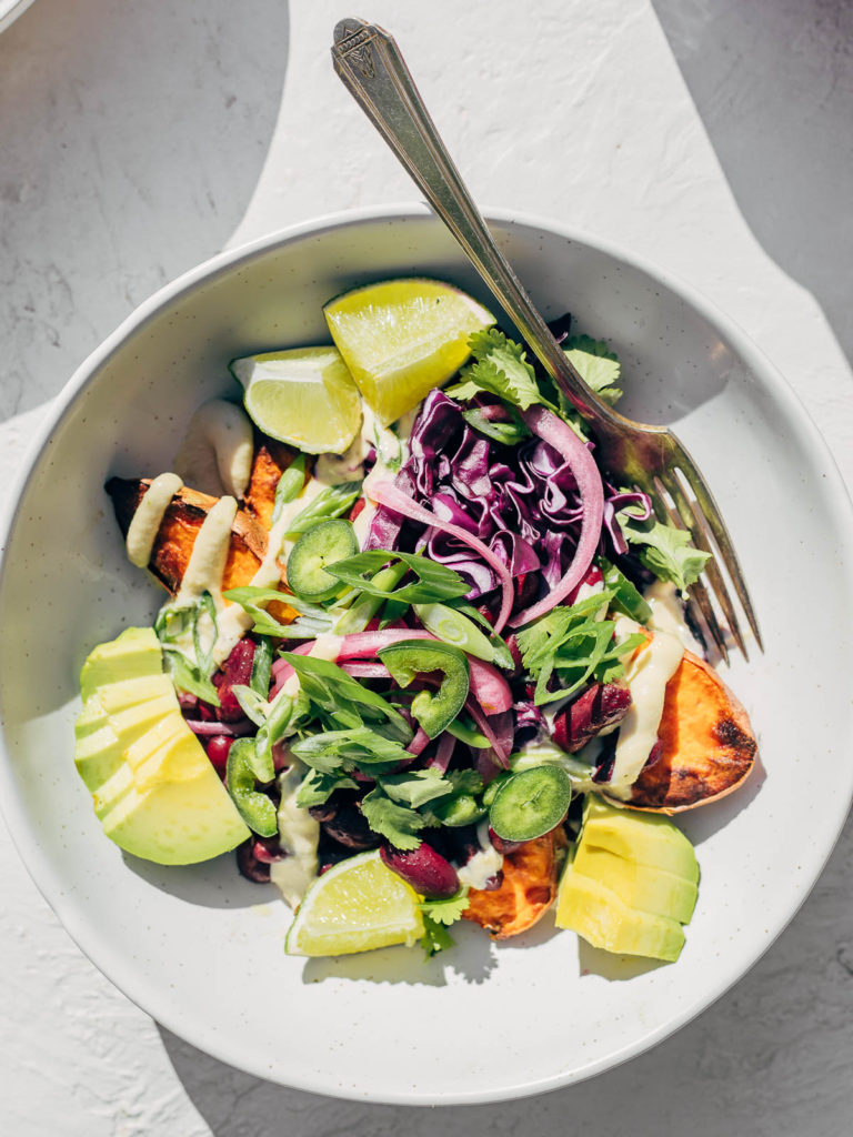 Fully loaded baked yam with avocado, beans, and pickled red onions