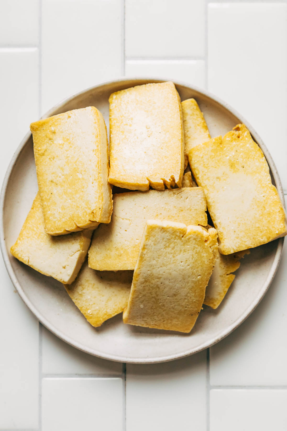 Slices of glofen fried tofu on a plate, ready to be turned into teriyaki.