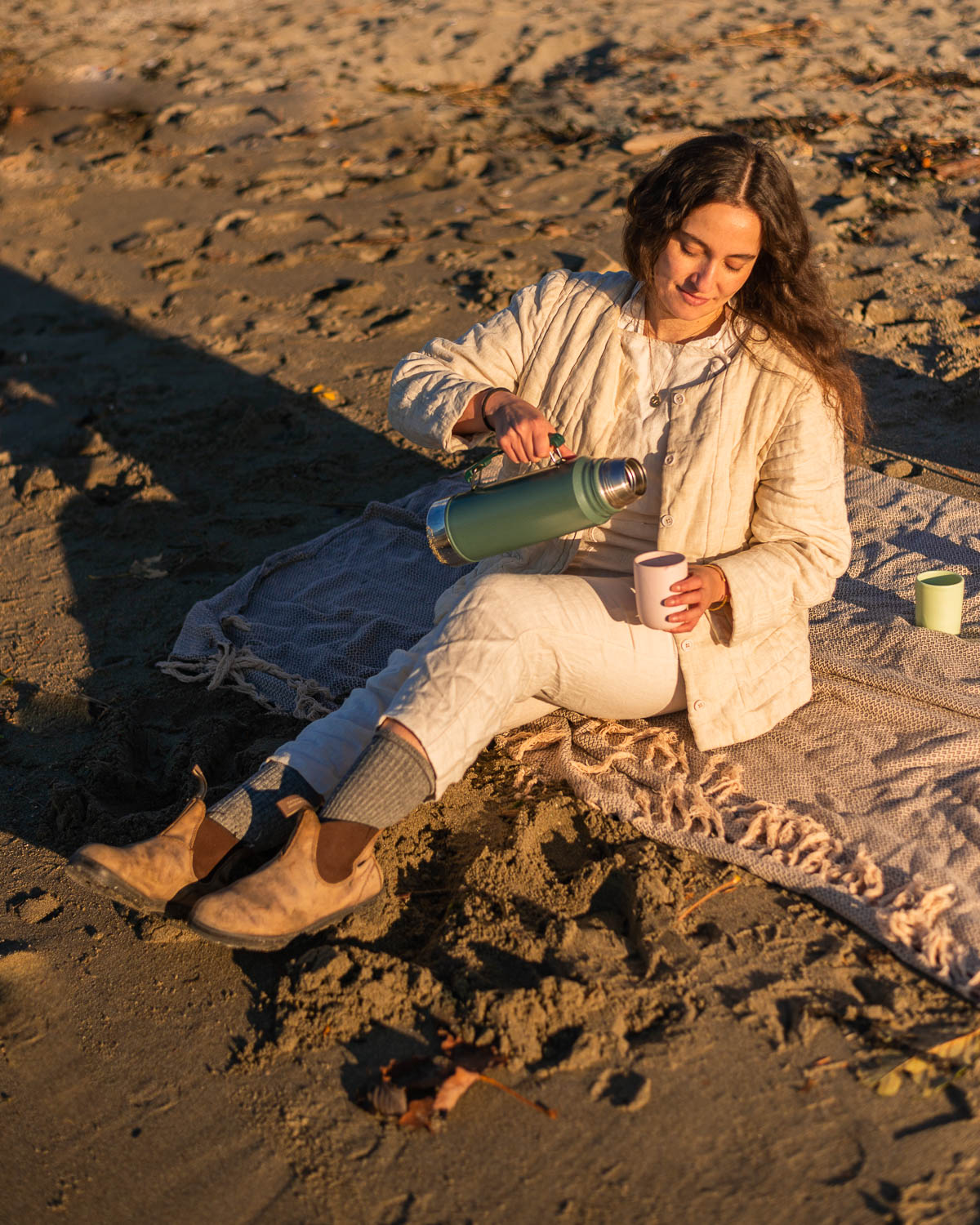 Women in a white outfit sitting on a blanket on a beach pouring coffee from a thermos.