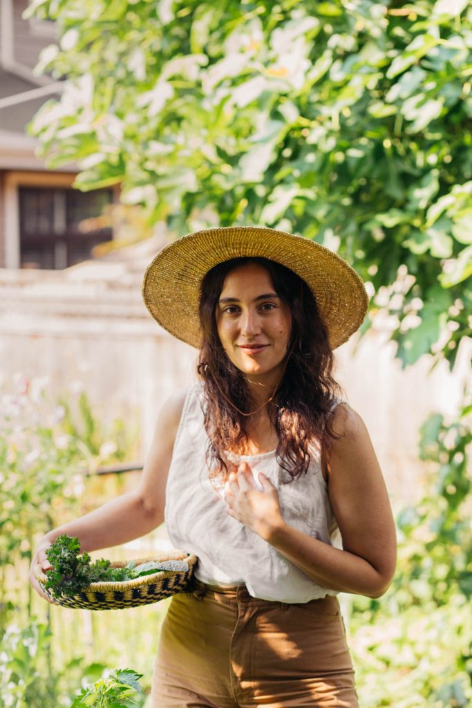 Woman in a garden with a straw basket and a straw hat.