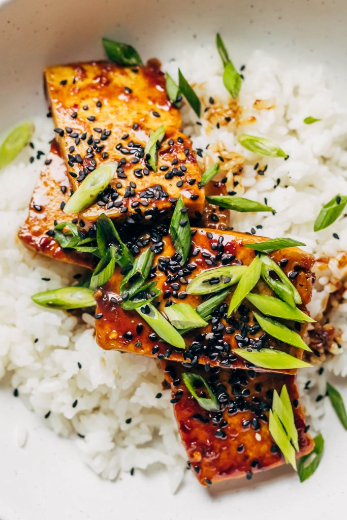 Close up pf sticky teriyaki on white rice with green onions and black sesame seeds.