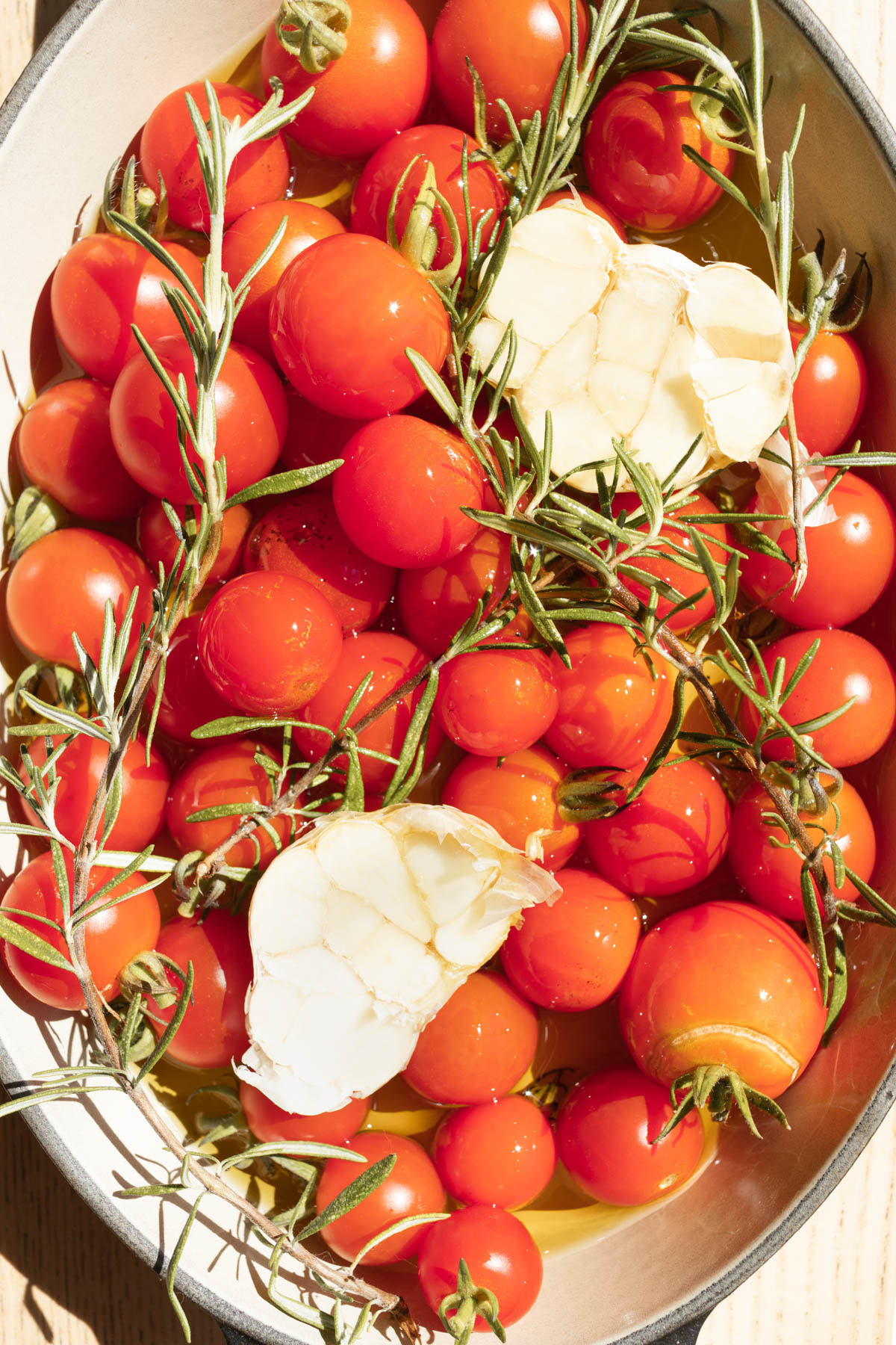 A close up of cherry tomatoes with garlic and rosemary.