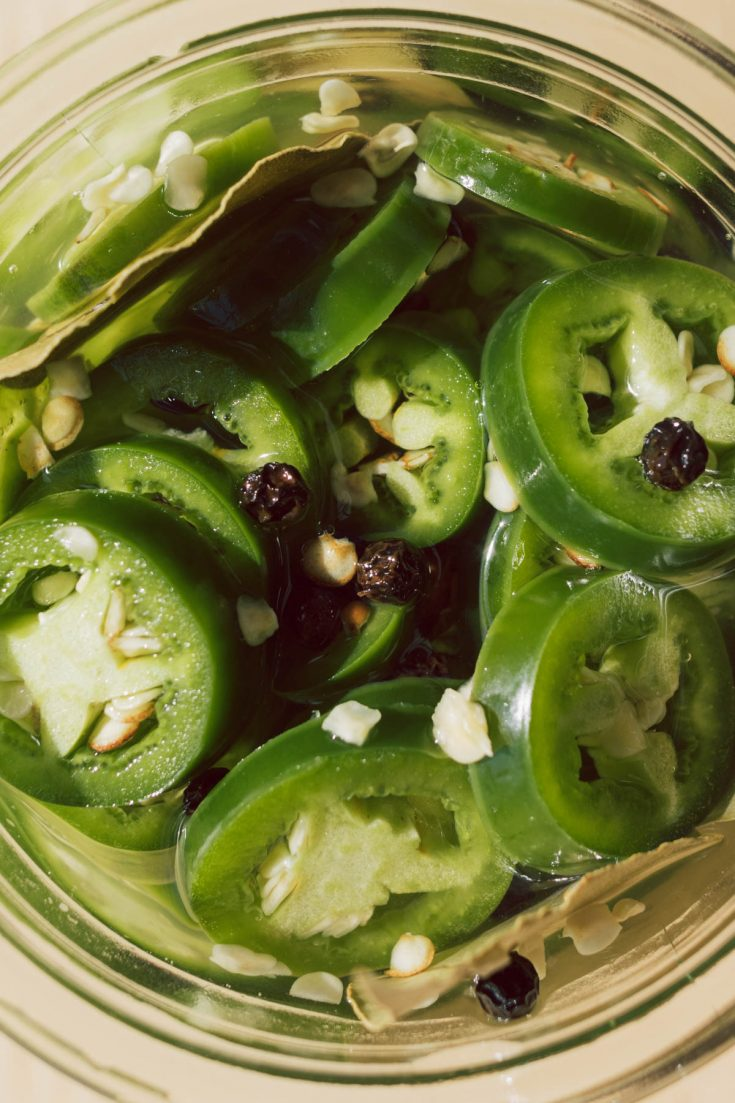 Close up of sliced pickled jalapeños in a glass jar.